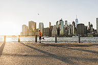 USA, Brooklyn, man jogging in front of Manhattan skyline in the evening - UUF09317