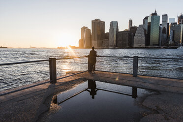 USA, Brooklyn, back view of woman leaning on railing looking at view at sunset - UUF09320