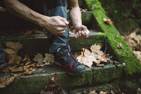Legs of a hiker sitting on stairs lacing his shoes - RAEF01550