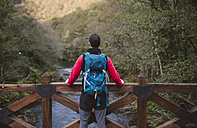 Hiker standing on bridge above a river looking at view - RAEF01562