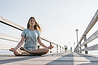 Young woman practising yoga on jetty - KNSF00671