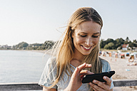 Smiling young woman using smartphone - KNSF00674