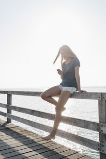 Young woman standing on jetty at backlight looking at cell phone - KNSF00677