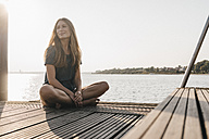 Portrait of smiling young woman relaxing on jetty - KNSF00680