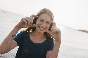 Portrait of happy young woman shaping finger frame - KNSF00683