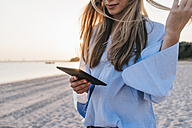 Young woman using tablet on the beach, partial view - KNSF00698