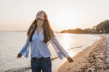 Young woman on the beach at sunset - KNSF00701