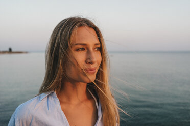 Portrait of young woman in front of the sea at sunset - KNSF00704