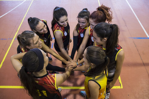 Female volleyball team huddling and stacking hands - ABZF01566