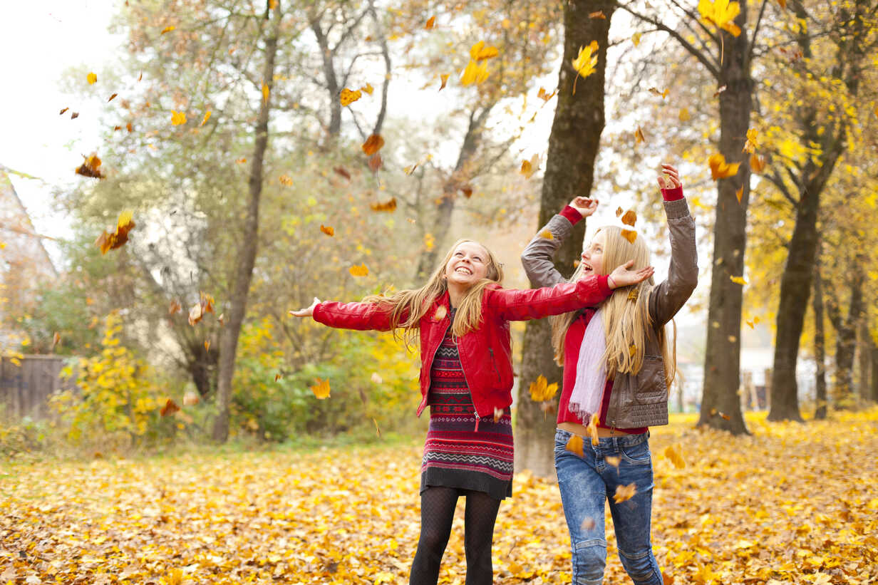 Two happy girls throwing autumn leaves in the air - MAEF12059 - Roman Märzinger/Westend61