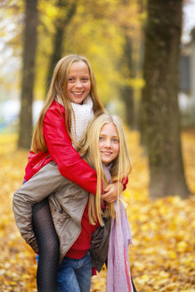 Girl giving her best friend a piggyback ride in autumn - MAEF12065