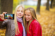 Two smiling girls taking selfie with cell phone in autumn - MAEF12068