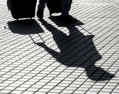 Shadow on pavement of a man pulling wheeled luggage - EJW00808