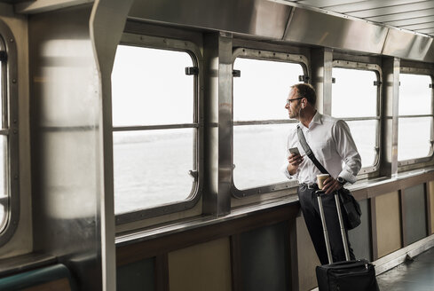 Businessman on a ferry looking out of window - UU09343