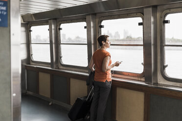 Woman on a ferry looking out of window - UU09346