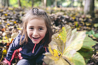 Portrait of laughing little girl standing in the woods, holding autumn leaves - DAPF00477