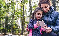 Mother and little daughter playing with smartphone in the woods - DAPF00489