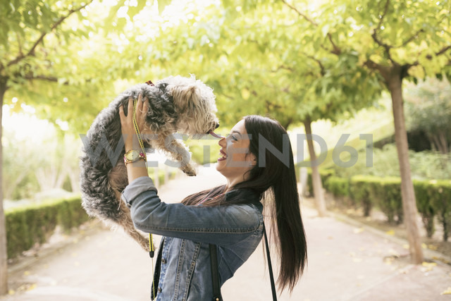 Happy young woman with her dog in a park - JASF01303