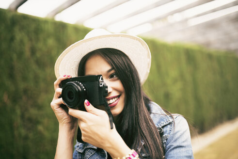 Young woman wearing hat taking picture with camera - JASF01306