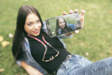 Young woman lying on meadow taking selfie with cell phone - JASF01312