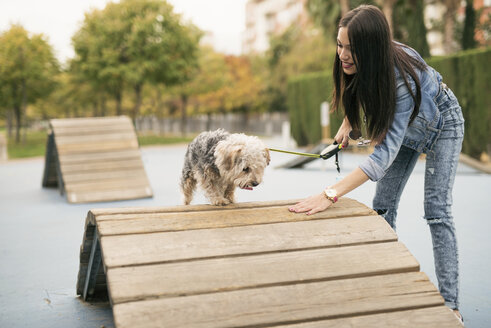 Young woman training her dog in a park - JASF01315