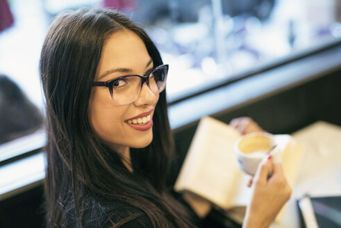 Smiling young woman in a coffee shop with book - JASF01318