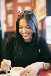 Portrait of laughing young woman in a coffee shop - JASF01321