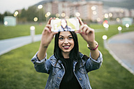 Young woman taking selfie with cell phone at twilight - JASF01324