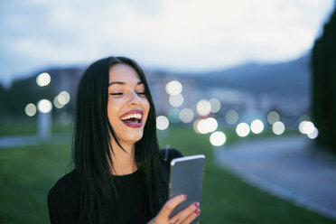 Portrait of laughing young woman with smartphone - JASF01327