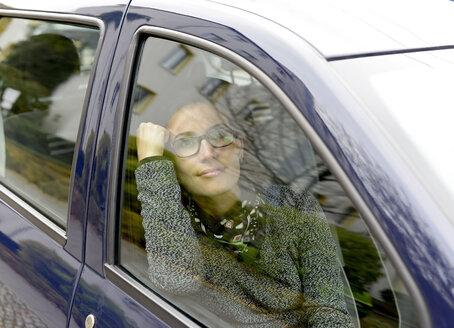 Woman looking through car window - BFRF01792