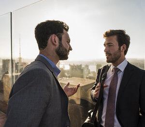 USA, New York City, two businessmen talking on Rockefeller Center observation deck - UU09354