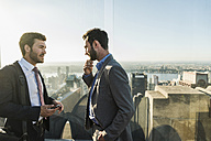 USA, New York City, two businessmen talking on Rockefeller Center observation deck - UU09357