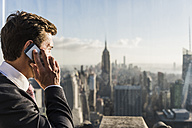 USA, New York City, man talking on cell phone on Rockefeller Center observation deck - UU09360