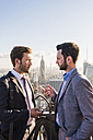 USA, New York City, two businessmen talking on Rockefeller Center observation deck - UU09366