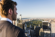 USA, New York City, man looking on cityscape on Rockefeller Center observation deck - UU09372