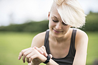 Smiling young woman checking her smartwatch - TAMF00828
