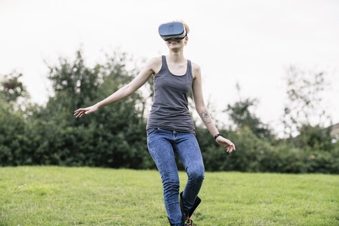 Smiling young woman using Virtual Reality Glasses outdoors - TAMF00834