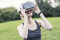 Smiling young woman using Virtual Reality Glasses outdoors - TAMF00837