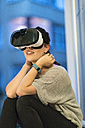 Young woman sitting beside window wearing Virtual Reality Glasses - TAMF00846
