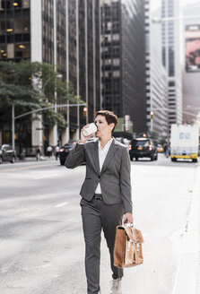USA, New York City, businesswoman in Manhattan with takeaway coffee - UUF09386