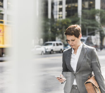 USA, New York City, businesswoman in Manhattan looking on cell phone - UUF09389