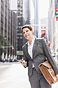 USA, New York City, businesswoman in Manhattan with cell phone - UUF09392
