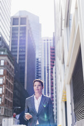 USA, New York City, businesswoman in Manhattan with with cell phone and earphones - UUF09401