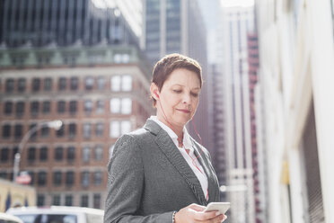 USA, New York City, businesswoman in Manhattan with with earphones looking on cell phone - UUF09404
