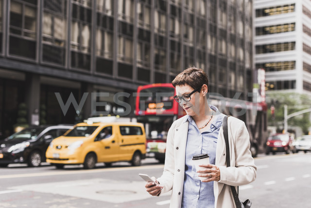 USA, New York City, woman in Manhattan looking on cell phone - UUF09410 - Uwe Umstätter/Westend61