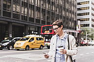 USA, New York City, woman in Manhattan looking on cell phone - UUF09410