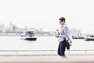 USA, New York City, businesswoman walking at East River reading document - UUF09413