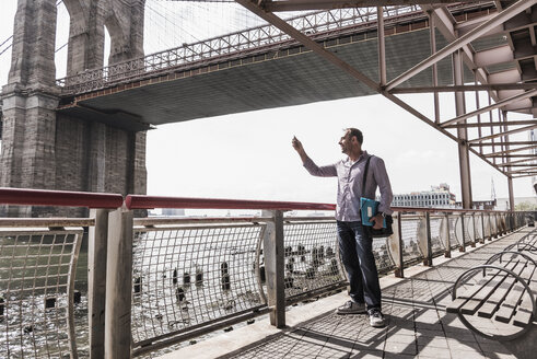 USA, New York City, man at East River holding cell phone - UUF09422