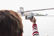 USA, New York City, woman at East River taking cell phone picture of Brooklyn Bridge - UUF09428