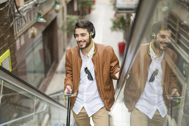 Smiling man with cell phone and headphones on escalator - JASF01331
